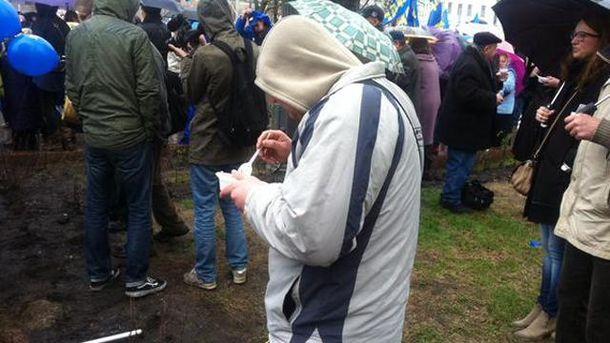 Учасник мітингу їсть кашу