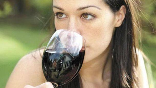 Насолоджується червоним вином